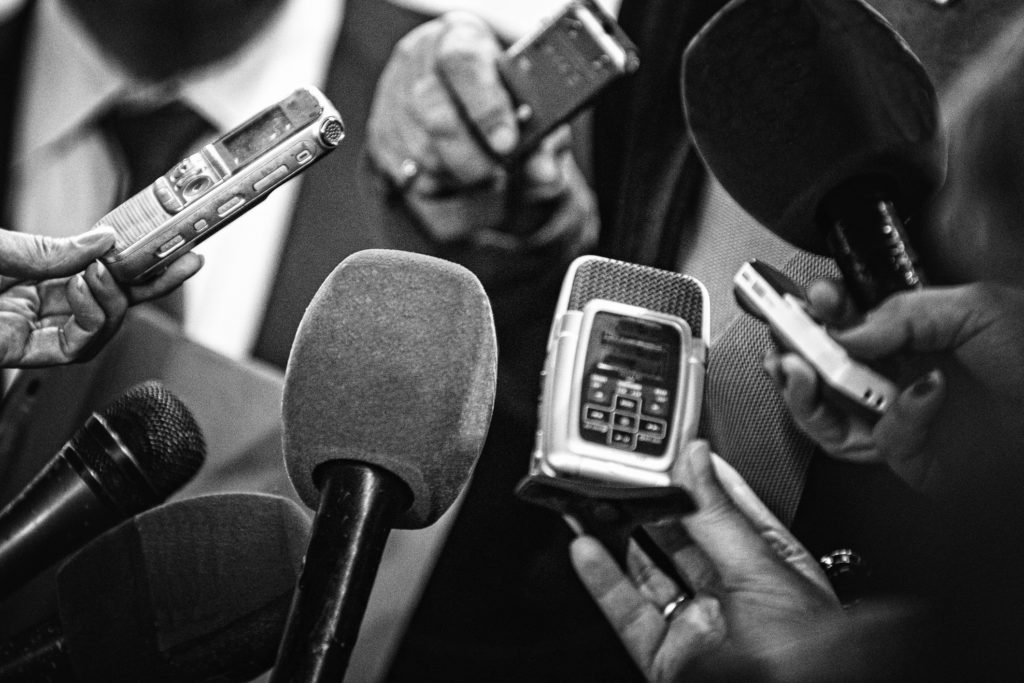 Journalists with recording equipment flocking around important people. Black and white retro style processing